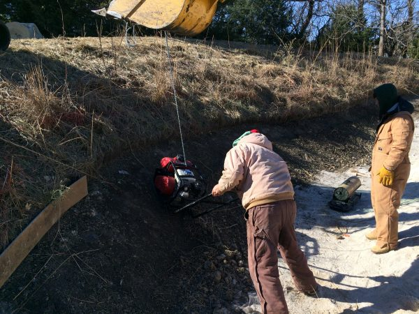 Using a vibratory soil compactor to provide firm bunker face for players