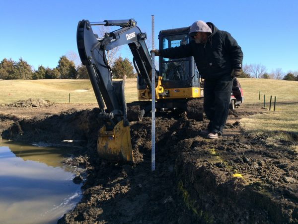 Approximately 1,600 cubic feet of soil were hauled out of the pond.  Daryl is showing a depth of three feet of soil above water line being removed.